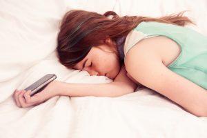 Teenage girl asleep holding mobile phone