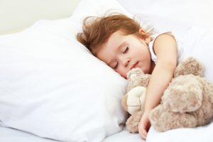 child little girl sleeps in the bed with teddy bear